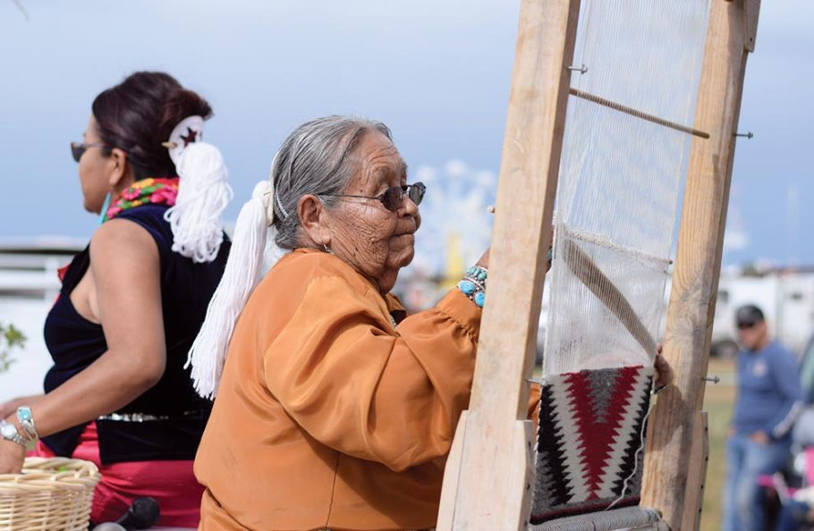 Navajo Times | Ravonelle Yazzie Esther, of Pine Hill, N.M., weaves a rug as she rides in the parade on Aug. 25 at the Ramah Navajo Fair and Rodeo.