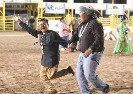 Navajo Times | Donovan Quintero Shar Redhouse entertains the crowd while dancing with one of the Davis Boys on Saturday night during the 72nd annual Navajo Nation Fair Cultural Showcase at the Dean C. Jackson Memorial Arena in Window Rock.