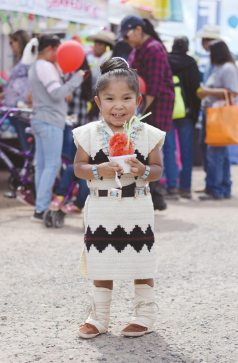 Navajo Times | Ravonelle Yazzie With a snow cone in hand, 4-year-old Kayden James cools off at the Navajo Nation Fair on Sept. 6.