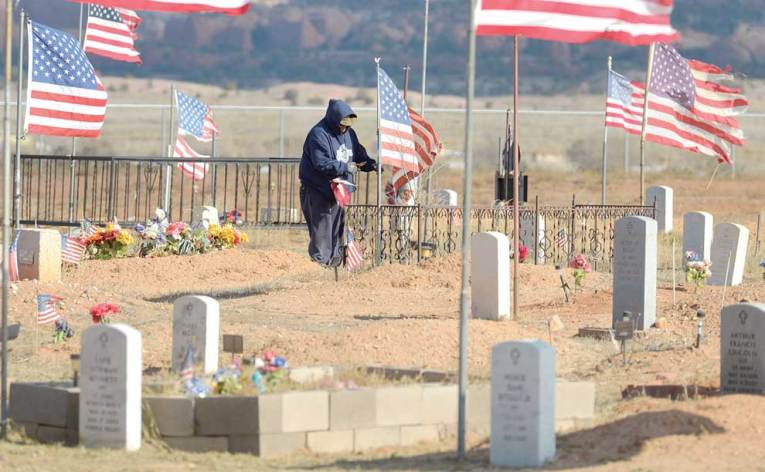 Navajo Times   Donovan Quintero A man replaces an old flag with a new one at the Veterans Cemetery on Veterans Day in Fort Defiance.