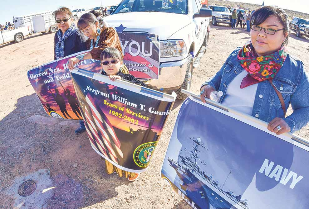 Navajo Times   Krista Allen From left to right, Marjorie Dougi, her daughter Maegan and nieces Leilani Nez, 7, and Brytina Ingel, prepare to walk with posters showing the names of their military veterans in the Veterans Day parade down Main Street in Tónaneesdizí on Nov. 10.