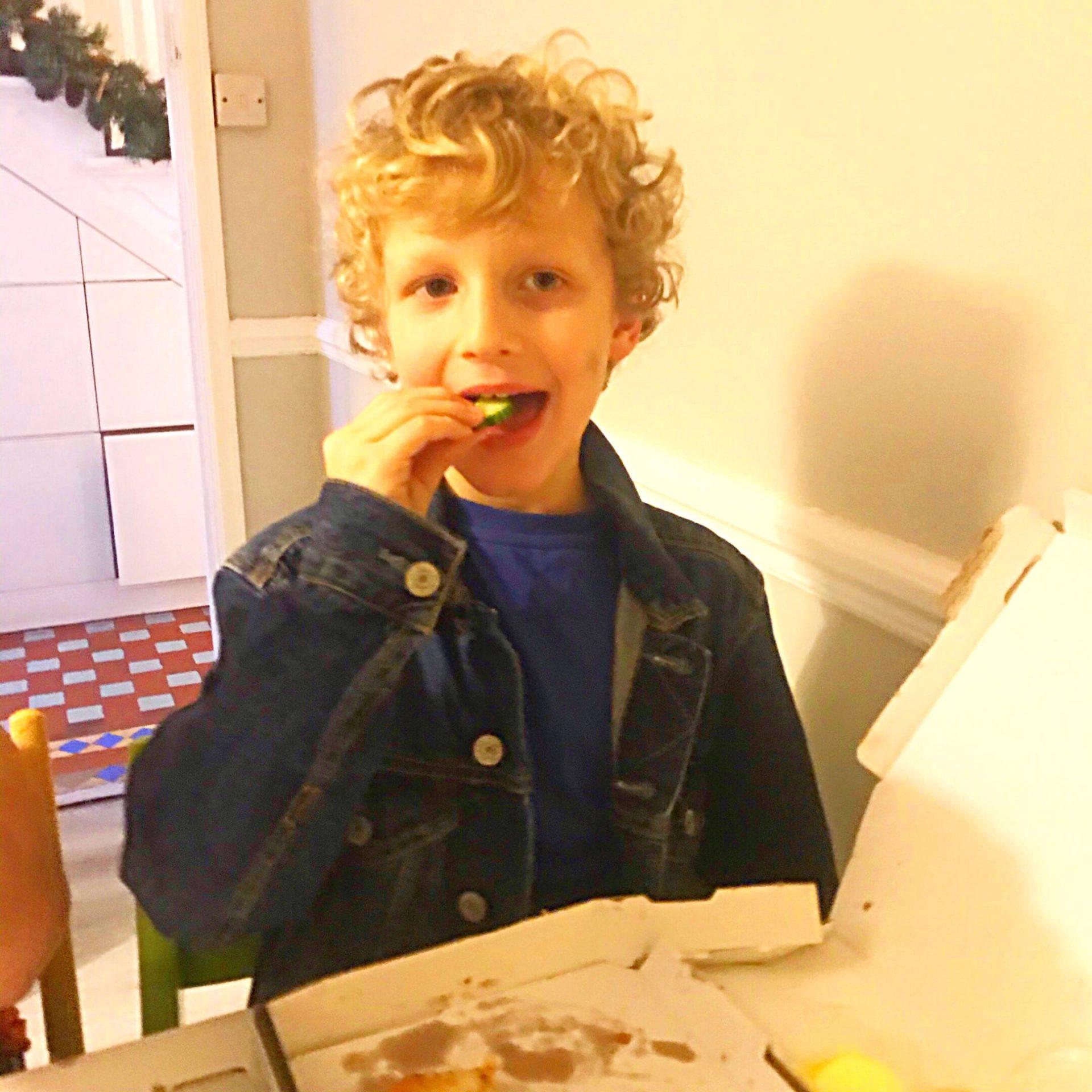 Boy eating cucumber on family night