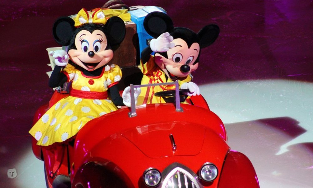 Minnie Mouse and Mickey Mouse waving hello from a red car on the ice at Disney on Ice