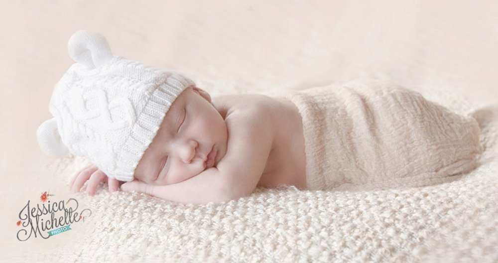 newborn sleeping on a blanket