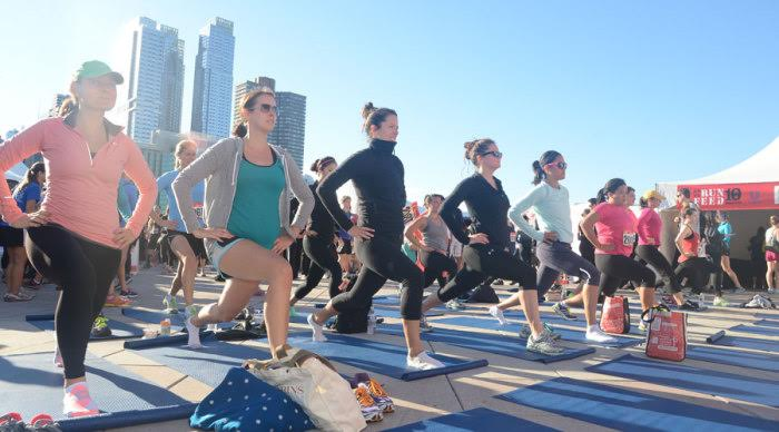 Photo of women doing lunges on mats in front of city background