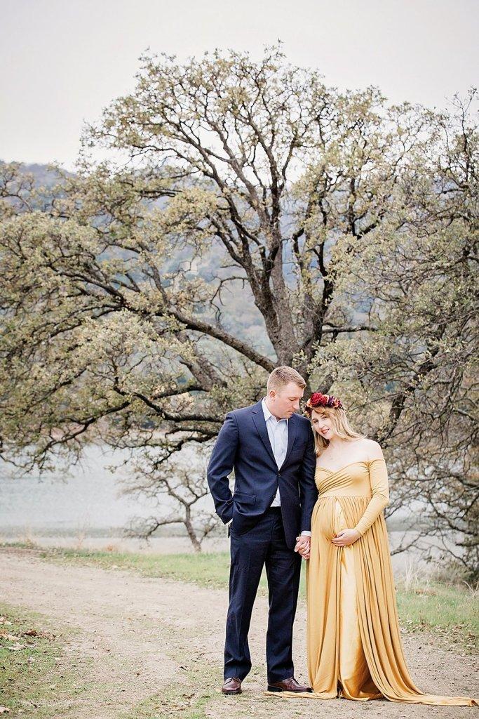 maternity photo of couple near tree