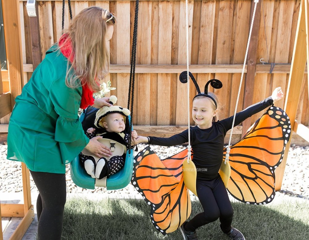 helping baby in a bee costume on a swing set while girl in butterfly costume sits on a swing with outstretched wings