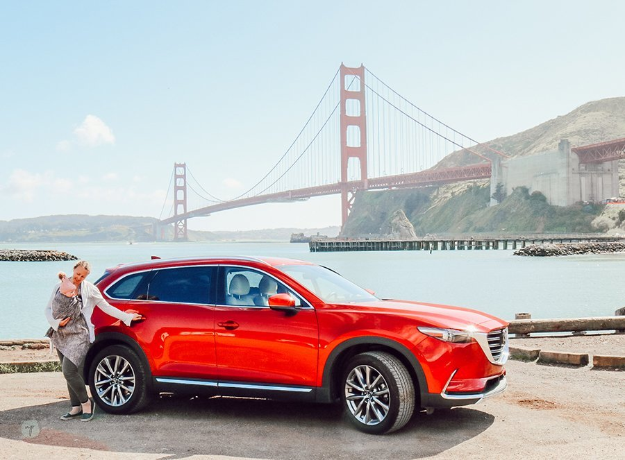 mom and baby standing by open door of a Mazda CX-9 in SF with Golden Gate Bridge in the background