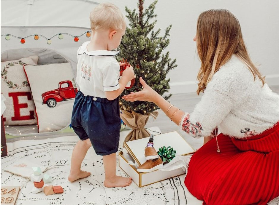 mom and toddler by mini Christmas tree