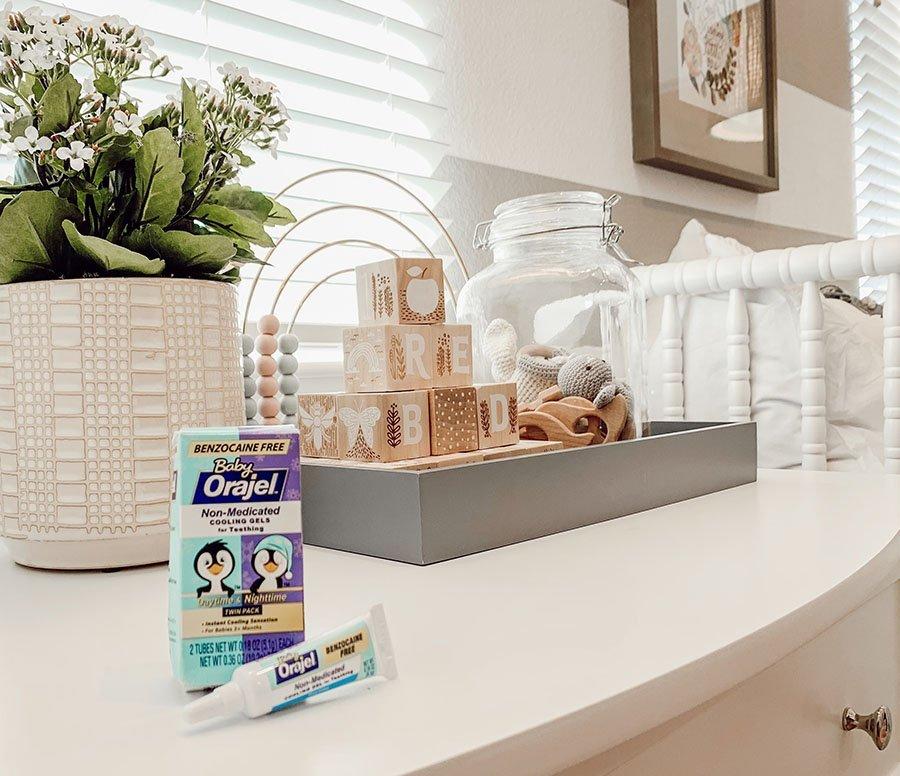 Orajel teething gels sitting on nursery room dresser