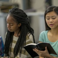 | A multi-ethnic group of high school age students are sitting together reading the Bible together during a Bible study.