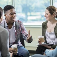 Building Relationships in a Small Group | Storytelling | The Navigators | Young African American man gestures while discussing something with a group of friends. They are listening intently to him as he talks.