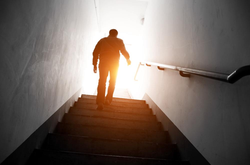 Finding Hope in Hard Times   Man walking upstairs into the light.