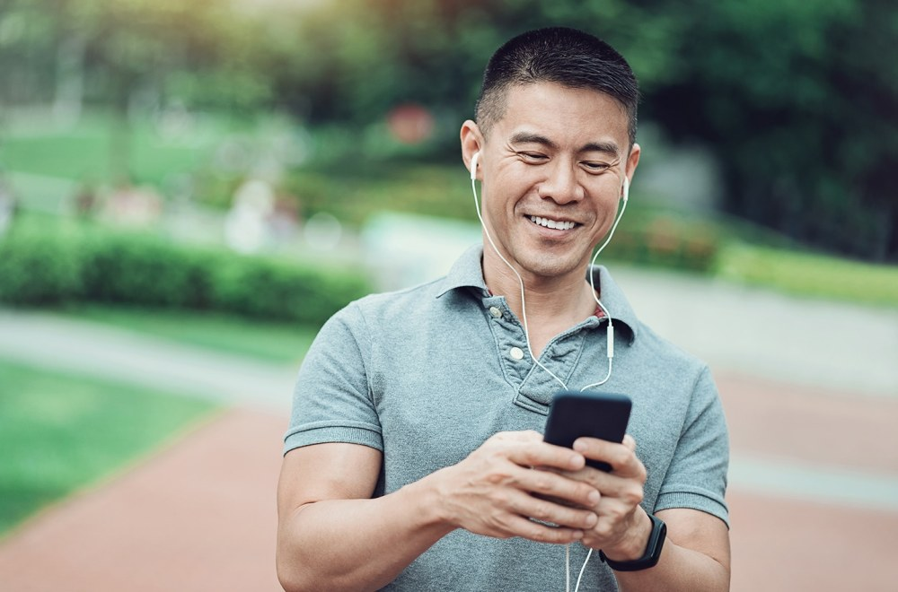 Asian ethnicity man listening to his phone in the park
