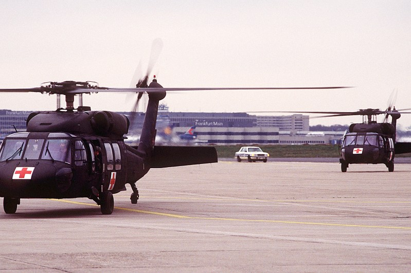Two 63rd Medical Evacuation Squadron UH-60 Black Hawk helicopters arrive at the base with injured sailors who are being evacuated to the United States. The men will be flown to Andrews Air Force Base, Md., and then to Brooke Army Medical Center in Texas for treatment of burns.