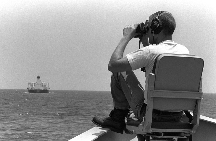 Mess Management Specialist 2nd Class Williams Hendrickson scans for mines from the bow of the guided missile frigate USS Nicholas (FFG-47) on June 1, 1988, during an Earnest Will convoy. (PHCS Mitchell/U.S. Navy)