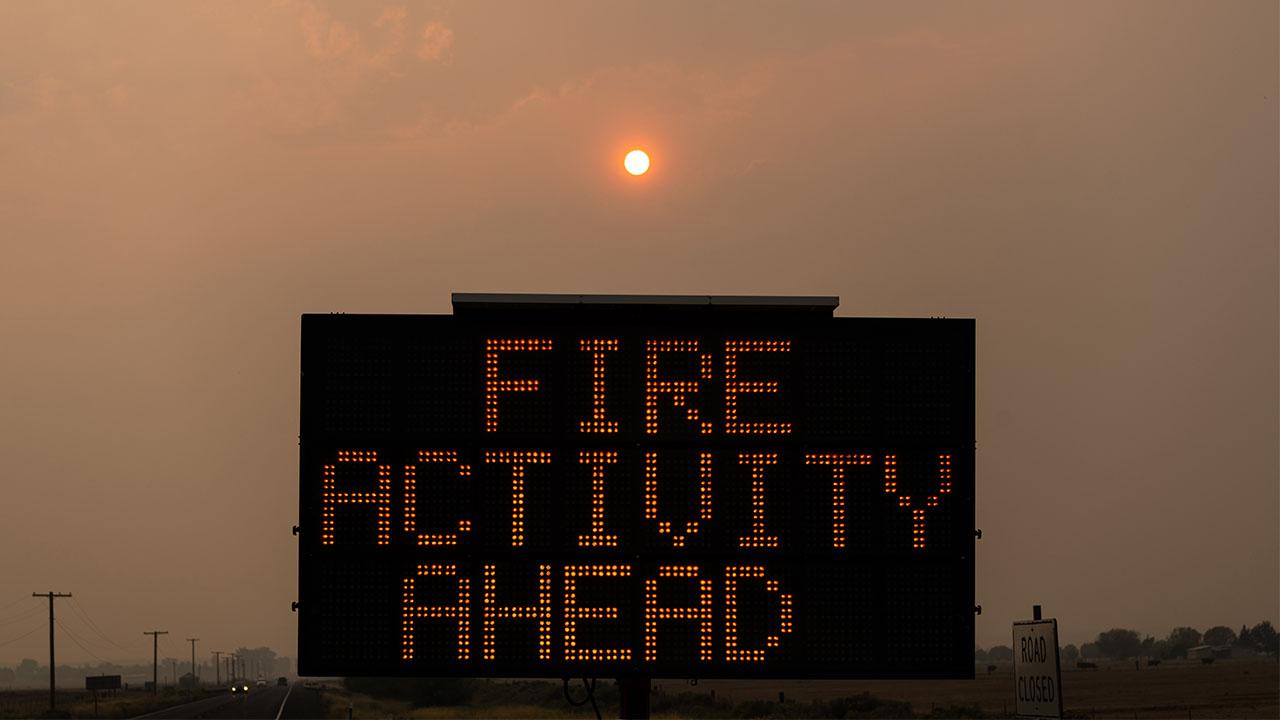 fire activity ahead sign wildfire hazy sun