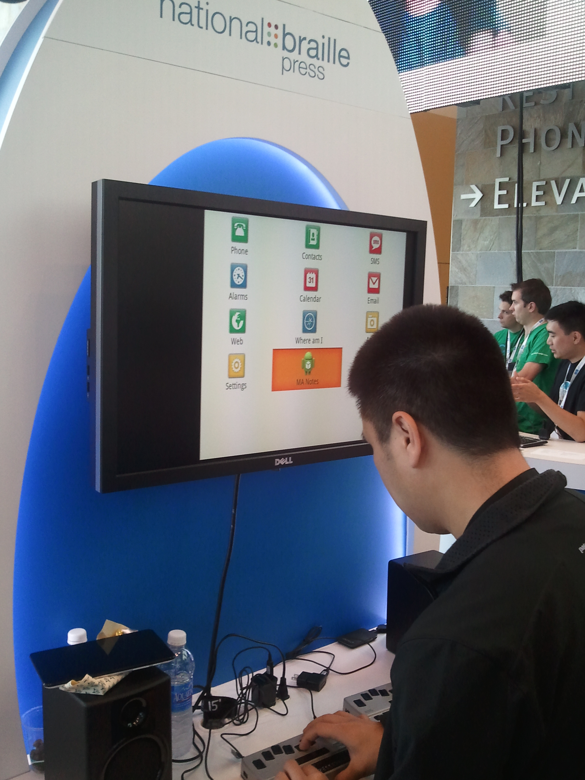 A photo of a blind person field testing the b2g that is connected to a large output screen from NBP's booth at the Google I/O conference