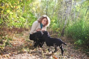 16444058-young-woman-plaing-with-black-labrador-retriever-puppy-in-the-autumn-forest