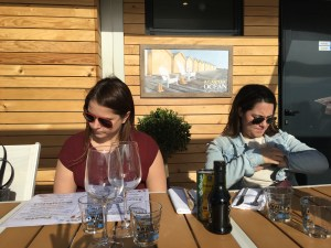 Steph and Sarah at o'key beach restaurant in Cannes - checking in on phones and menus