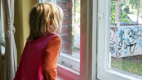 A child is standing by the window © dpa