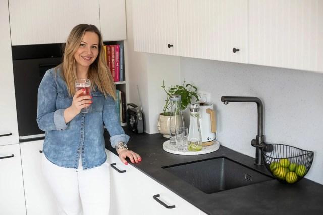 kobieta w kuchni ze szklanką napoju gazowaneg
