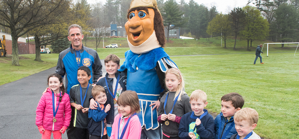 President Lane Glenn, the NECC Knight mascot, and several young children with awards around their neck for their fun run.