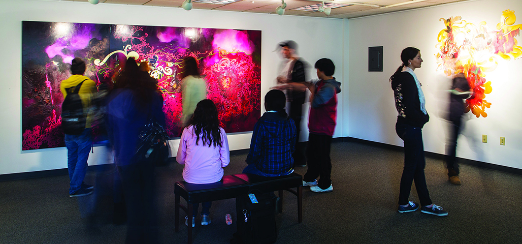 Several people gather around a large coloful painting hanging on a wall in the artspace.
