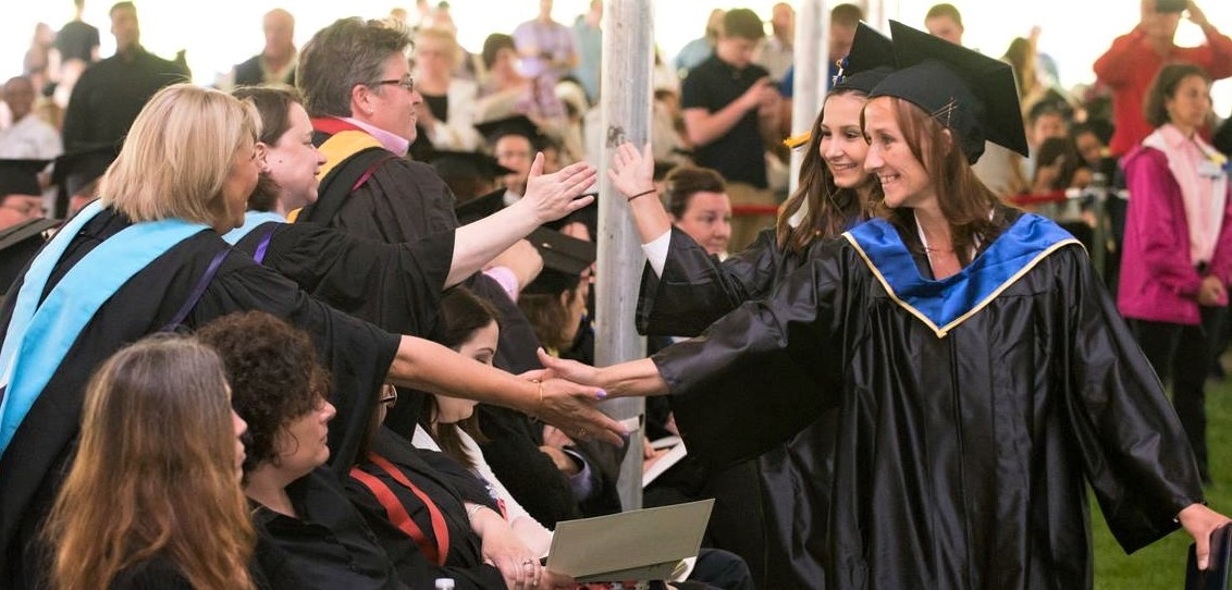 Graduate shake hands with people as they walk at commencement.