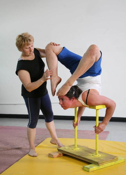 photo of a woman training a flexibility skill on handbalancing canes