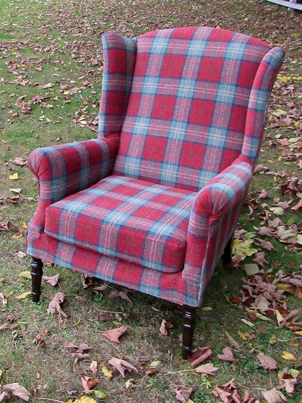 Parker Knoll Wingback Armchair covered in cherry/green tartan fabric (front view).