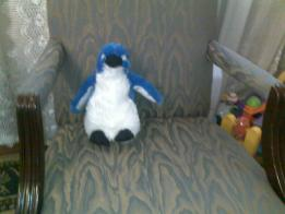 stuffed penguin sitting on a chair like it's interviewing