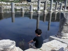 photo of child with broken roman columns in the background
