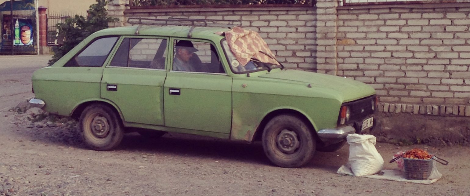 old car and a tired man sitting in it to sell vegetables