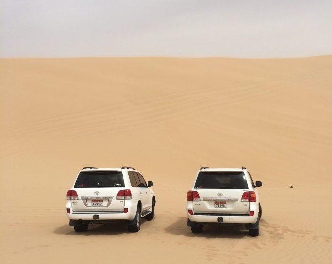 two white SUVs in the desert