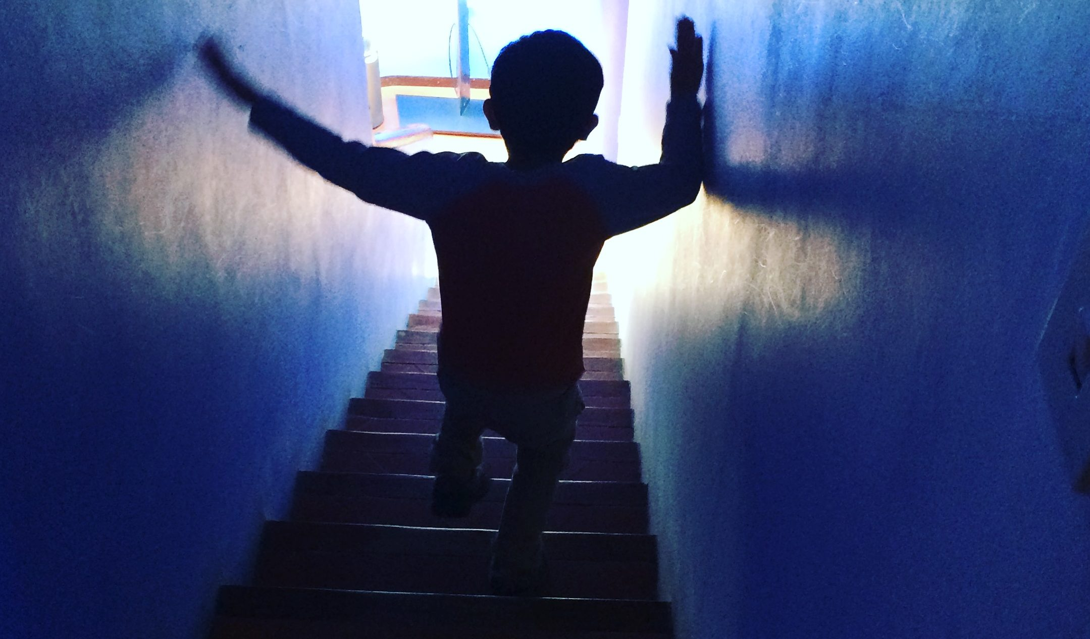 Child walking down a tunnel toward light.