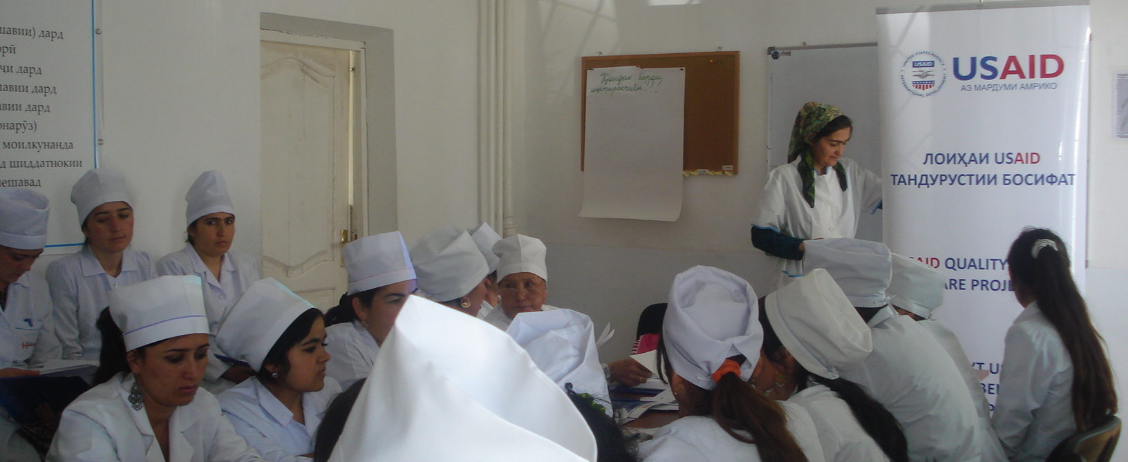 doctors in white coats by a USAID banner
