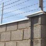 photo of brick wall with barbed wire across the top