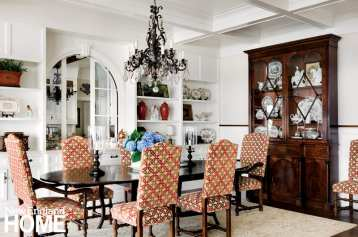 Antique chairs surround a reproduction dining table. The Georgian hutch holds a prized collection of Staffordshire.