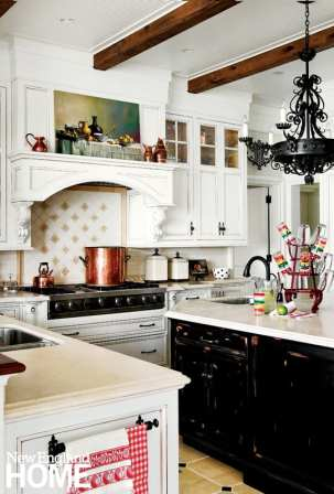 White cabinets, ceiling timbers and the distressed black paint on the island make the kitchen feel cottage cozy.