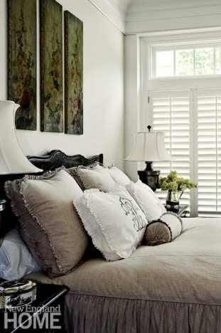 Wooden shutters offer privacy in a serene guest bedroom.