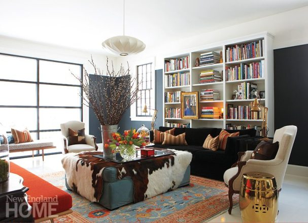 A colorful Oushak carpet sets the library's welcoming tone. The George Nelson pendant lamp adds a modern note, while classic articulating brass lamps from Michele Varian aid nighttime reading.