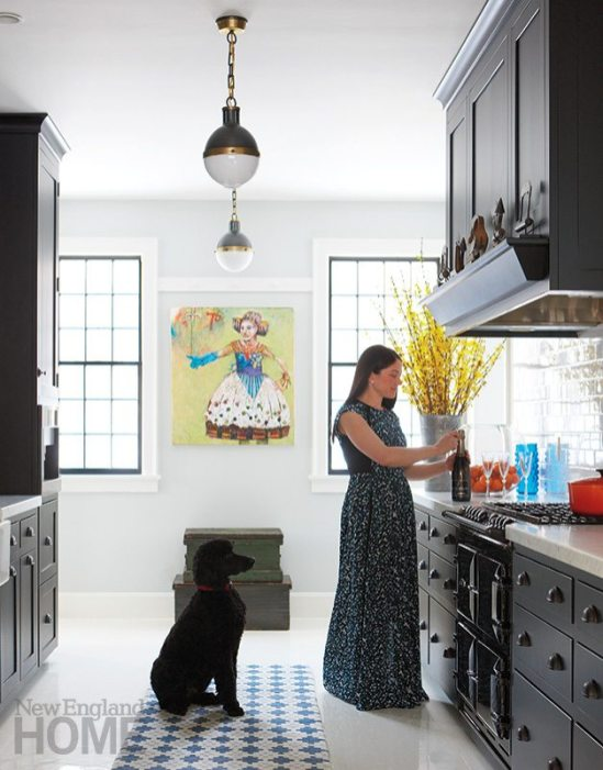 Dragoo and the family pet, Tauren Poodle, get ready to entertain. The lively painting in the kitchen is by Albuquerque, New Mexico, artist Deborah Donelson.