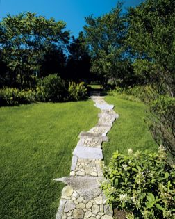 Granite and flat fieldstone shape a gently curving walkway.