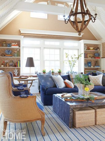The high-ceilinged family room strikes a nautical tone with shades of blue and sand.