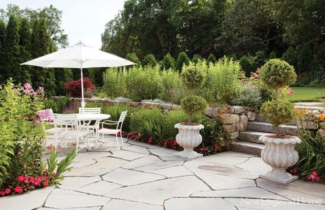 A terrace area allows for entertaining space and an open lawn lies just behind the stone wall.