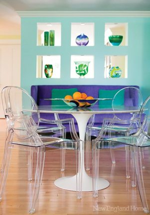 Louis Ghost chairs cozy up to a white pedestal dining table; a purple chenille sofa adds a pop of rich color.