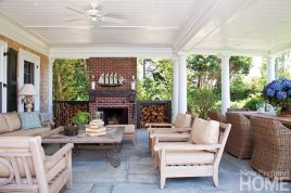 The covered porch at the back of the house lets the owners relax outdoors rain or shine. The chairs, the sofa and dining table are from Restoration Hardware, while the coffee table, side table and lamps are antiques store finds. Antique bricks were used to build the fireplace, and the metal ship's model on the mantel is also an antique.