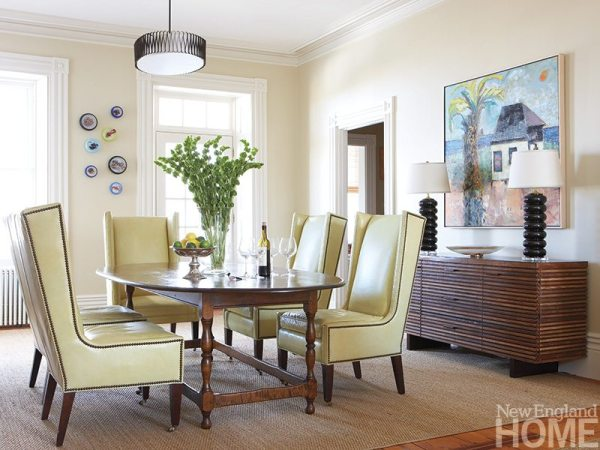 Designer Charlotte Barnes outfitted the dining room in an array of styles, anchoring the space with a timeless antique birds-eye maple table, then adding mid-twentieth-century chairs and a Crate & Barrel sideboard. A vibrant, Caribbean-inspired painting, purchased locally by the homeowners, adds a relaxed feel.