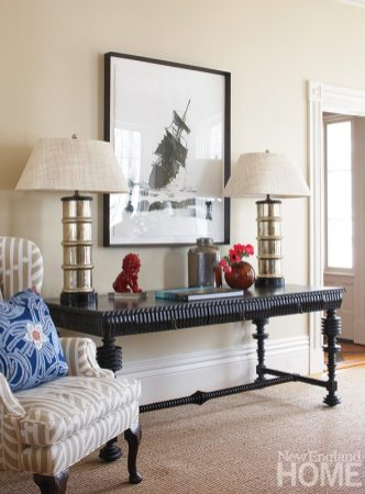 In the living room, antique mercury glass lamps sit atop a reproduction desk from HB Home.